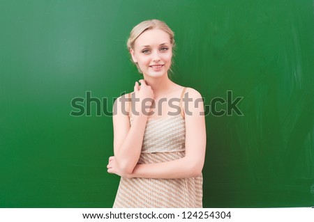 beautiful young teacher is standing near blackboard and looking at the camera