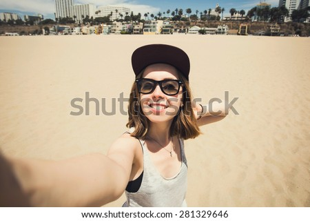 Beautiful young teen girl having fun and making selfie photos on Santa Monica beach in Los Angeles, California