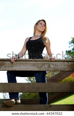 Beautiful young teen girl in black sequined tanktop - at wood railing