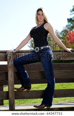 Beautiful young teen girl in jeans and black tanktop standing on wood railing