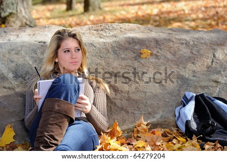 Beautiful young teen girl with backpack in autumn park - writing in notebook
