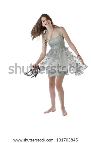 Beautiful young teenage girl with long brown hair dances in lacy silver party dress. Vertical, isolated on white with copy space. - stock photo