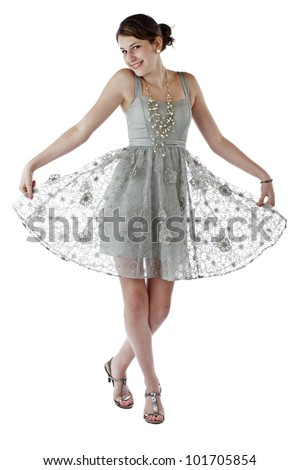 Beautiful young teenage girl with long brown hair hold skirt out and dances in lacy silver party dress. Vertical, isolated on white with copy space.