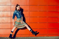 Beautiful young teenager hipster girl posing, going, runs near urban red wall background in skirt and jeans jacket on the sunset.