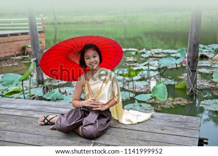 Beautiful young Thai girl in traditional dress costume red umbrella , sit near river side .floating market .Thai  culture Costume fashion
