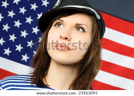 beautiful young thoughtful sailor standing opposite an American flag