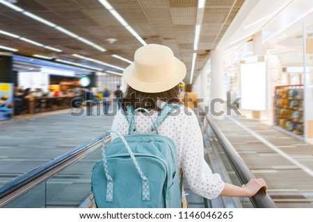 Beautiful young tourist girl wearing cream hat with green backpack on speedwalk in international airport to travel on weekends,motion blur,Travel departure concept. #1146046265