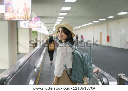 Beautiful young tourist girl wearing cream hat with green backpack on speedwalk in international airport to travel on weekends,motion blur,Travel departure concept. #1213613704