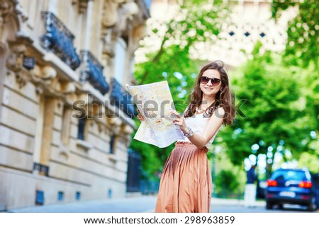 Beautiful young tourist in long skirt on a street of Paris near the Eiffel tower on a summer day, looking at the map and planning her itinerary