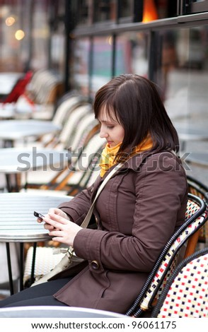 Beautiful young tourist in Paris sending sms from Parisian street cafe