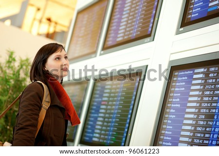 Beautiful young tourist in the airport looking at the flight board