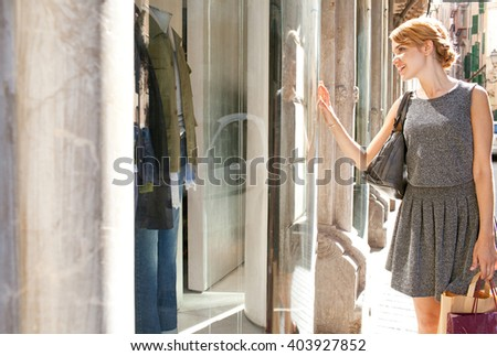 Beautiful young tourist woman carrying shopping bags walking in city fashion stores, joyfully smiling looking at shop windows, sunny outdoors. Consumer girl, exclusive expensive lifestyle exterior. #403927852