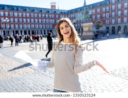 Beautiful young tourist woman happy and excited with map trying to find locations and monuments in Plaza Mayor Madrid, Spain, Looking cheerful and joyful. In tourism and travel around Europe. #1350523124