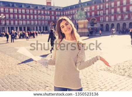 Beautiful young tourist woman happy and excited with map trying to find locations and monuments in Plaza Mayor Madrid, Spain, Looking cheerful and joyful. In tourism and travel around Europe. #1350523136