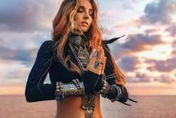 beautiful young tribal style woman holding hands pray namaste on the beach at sunset