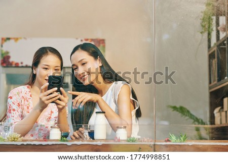 Beautiful young Vietnamese female friends checking photos they just made on smartphone stock photo