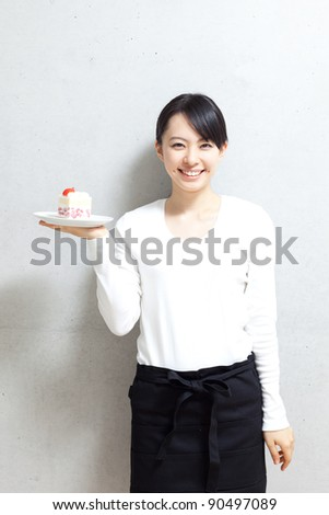 beautiful young waitress presenting plate of dessert