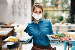 Beautiful young waitress with face protective mask working in exclusive restaurant. Coronavirus or Covid-19 concept.
