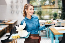 Beautiful young waitress working in exclusive restaurant.