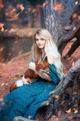 Beautiful young  white hair woman in a blue medieval dress with crown and red fox in autumn forest. Fairytale fantasy scene