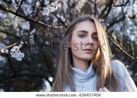 Beautiful young with long blond hair looks in camera. Model stands in park on blossom branches background. She dressed in white pullover. Close-Up.