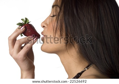 Beautiful young woman about to eat a strawberry