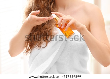 Beautiful young woman after bath with oil on blurred background