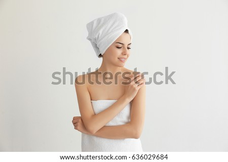 Beautiful young woman after shower on light background