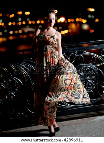 Beautiful young woman against night shined city.