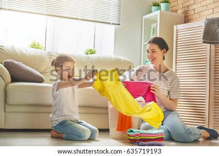 Beautiful young woman and child girl little helper are having fun and smiling while doing laundry at home. #635719193