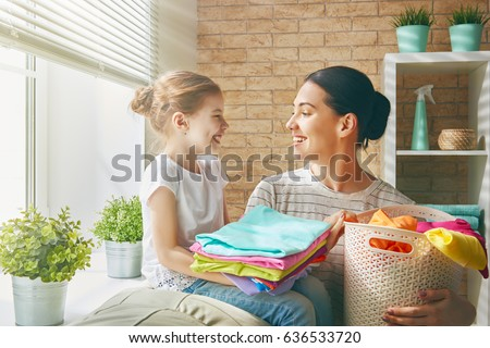 Beautiful young woman and child girl little helper are having fun and smiling while doing laundry at home. #636533720