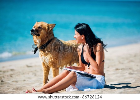 Beautiful young woman and dog on the beach