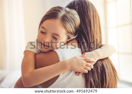 Beautiful young woman and her charming little daughter are hugging and smiling #495692479