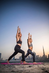 Beautiful young woman and her little daughter doing yoga together at sunset in Dubai. With city view. Skyline Dubai