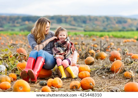 Beautiful young woman and little kid daughter, girl having fun with farming on a pumpkin patch. Traditional family festival with children, thanksgiving and halloween concept. #425448310