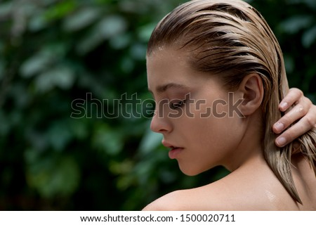 Beautiful young woman applies a balm, shampoo or conditioner to her damaged hair  front of plant tropical green leaves background.  SPA, bodycare, haircare  and skincare.  Close up, selective focus.