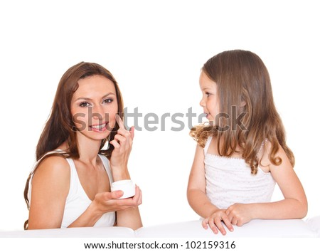 Beautiful young woman applying cream, little girl looking at her
