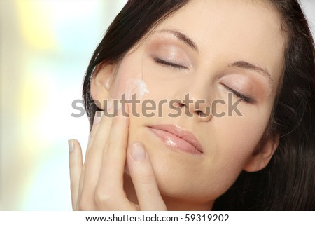 Beautiful young woman applying cream on her face.