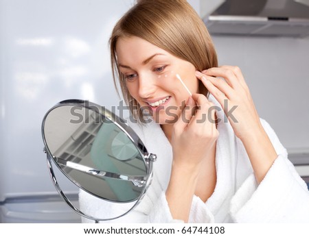 beautiful young woman applying cream on her face at home - stock photo