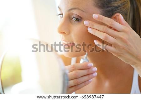 Beautiful young woman applying eye concealer on
