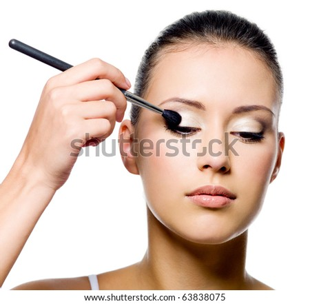 beautiful young woman applying eyeshadow with brush on white background - stock photo