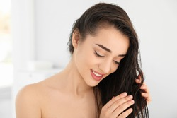 Beautiful young woman applying hair conditioner in bathroom