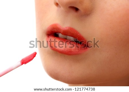 beautiful young woman applying lip gloss, isolated on white