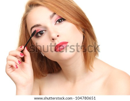 Beautiful young woman applying mascara on her eyelashes