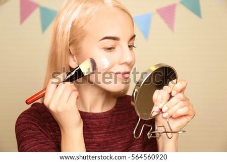 Shutterstock Beautiful young woman applying moisturizing cream to face