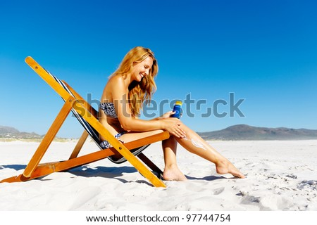 Beautiful young woman applying sunblock to her legs while sitting on a beach in summer.