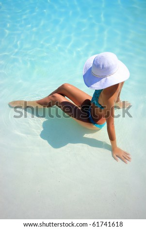 Beautiful young woman at a pool of a luxurious hotel