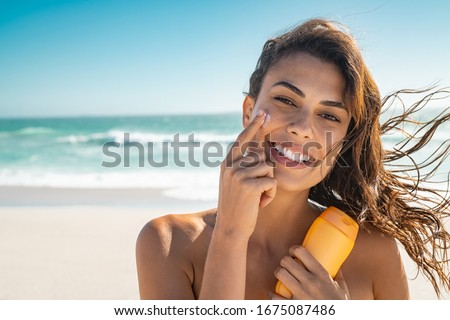 Beautiful young woman at beach applying sunscreen on face and looking at camera. Beauty latin girl applying suntan lotion at sea. Portrait of happy woman with healthy skin applying sunblock on cheek. Stock photo ©