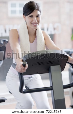 Beautiful young woman at gym, doing biking exercises