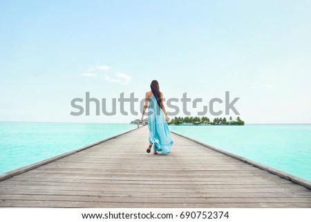 Beautiful young woman at sea resort #690752374